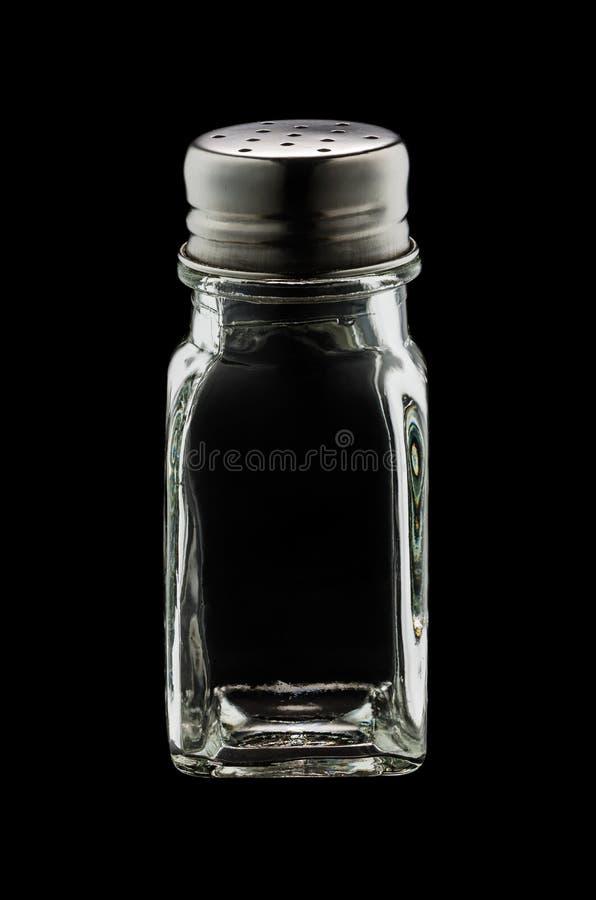 Un agitatore di vetro vuoto di sale isolato su fondo nero fotografie stock