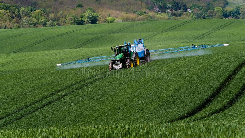 Un agricoltore che spruzza con un trattore di John Deere immagine stock