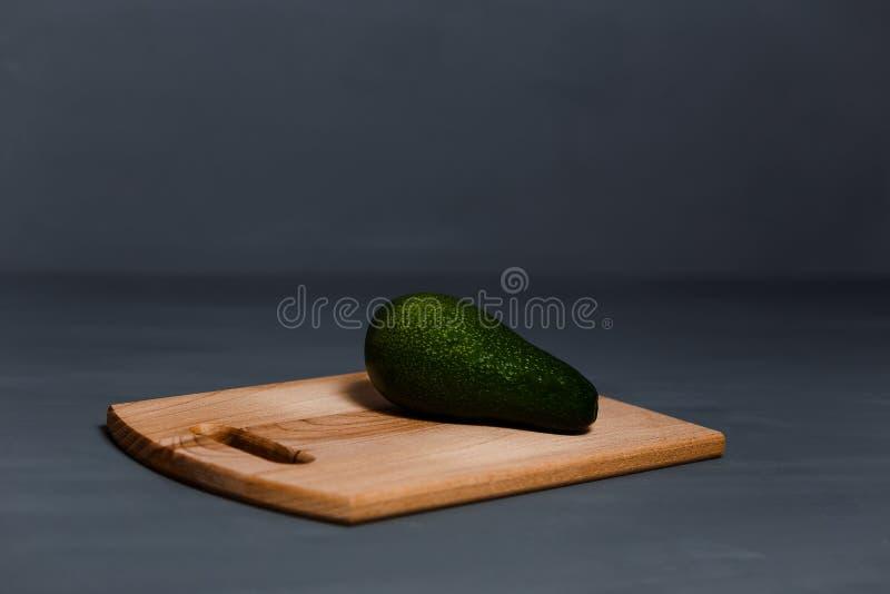 Un aguacate entero en una tabla de cortar de madera foto de archivo