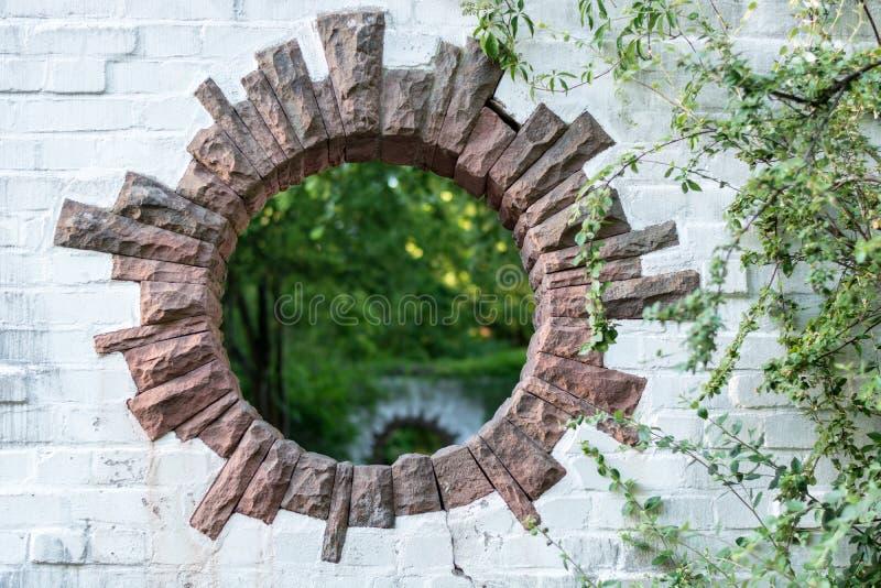 Un agujero redondo en una pared de ladrillo en un parque parece un portal imágenes de archivo libres de regalías
