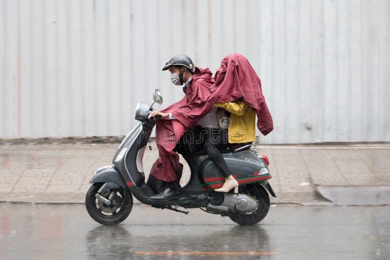 Un ajouter à l'imperméable monte sous la pluie sur une motocyclette photographie stock libre de droits