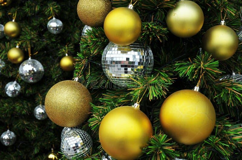 Un albero di Natale e palle di natale dorate e d'argento immagine stock