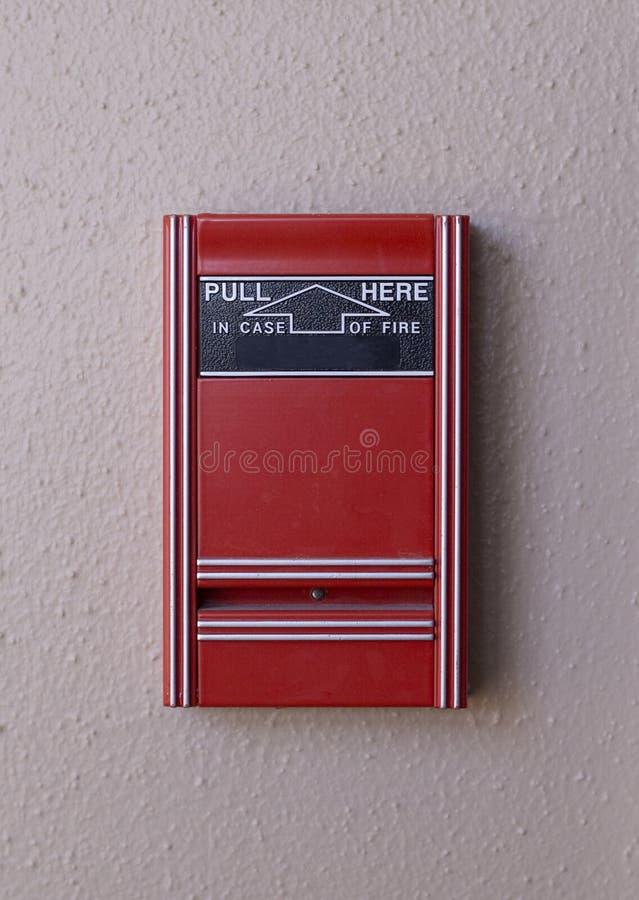 Un allarme antincendio rosso semplice su una parete strutturata bianca fotografie stock libere da diritti