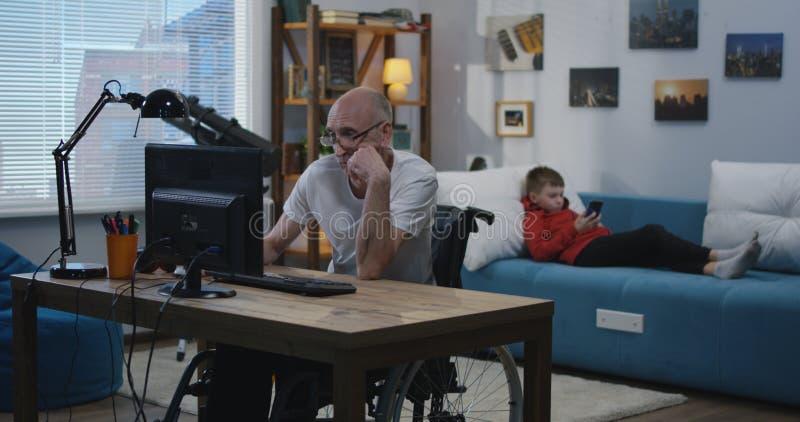 Un allegro disattiva l'uomo sul computer fotografia stock