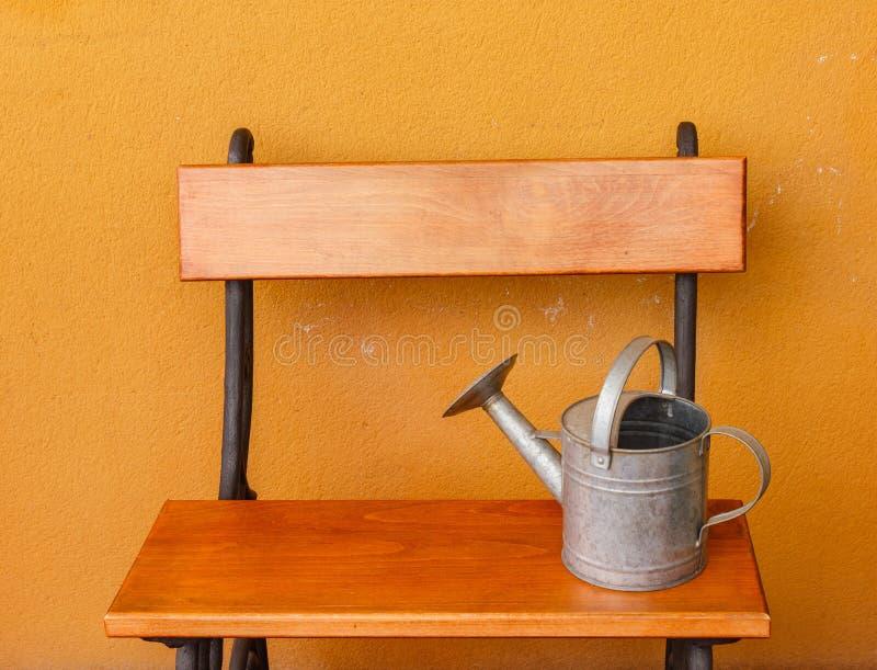 Un alluminio dell'annaffiatoio ha messo su un banco di legno immagine stock libera da diritti