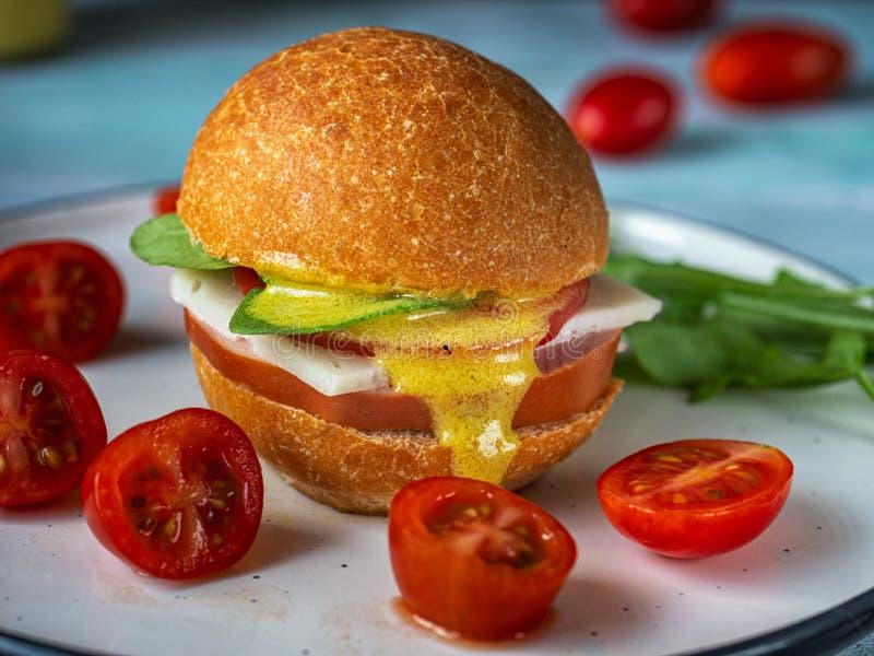 Un almuerzo rápido del tomate de la hamburguesa y de cereza y del arugula en una placa de cerámica brillante Tirado de gama cerca imagenes de archivo