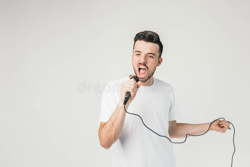 Un'altra immagine di un tipo in maglietta bianca che tiene un mic in mano destra ed in un cavo nella sua mano sinistra e che cant fotografia stock libera da diritti