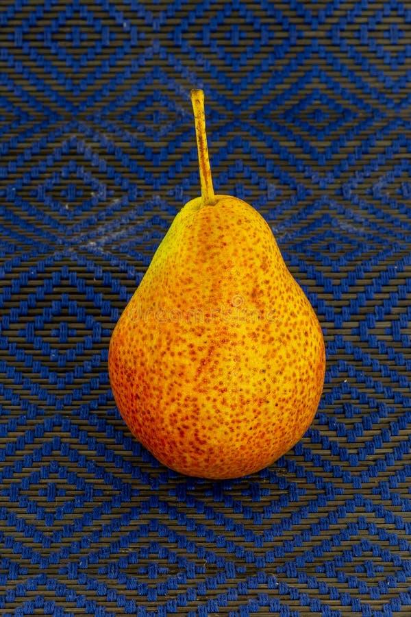 Un amarillo sabroso de la pera jugoso en la fruta apetitosa del almuerzo del almuerzo del bocado del fondo azul dappled reposterí imágenes de archivo libres de regalías
