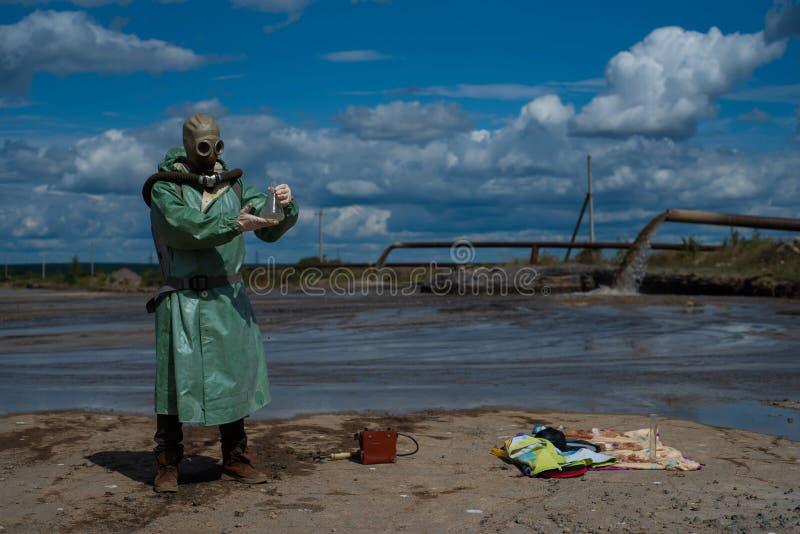 Un ambientalista con traje protector verde y máscara de gas toma una muestra de agua en un lago contaminado para investigación foto de archivo