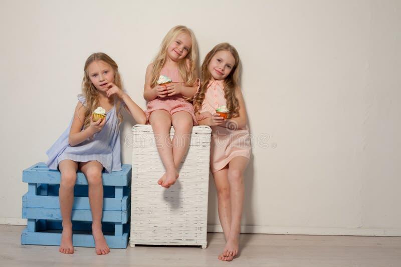 Un'amica di tre ragazze mangia la sorella della lecca-lecca della caramella fotografia stock libera da diritti