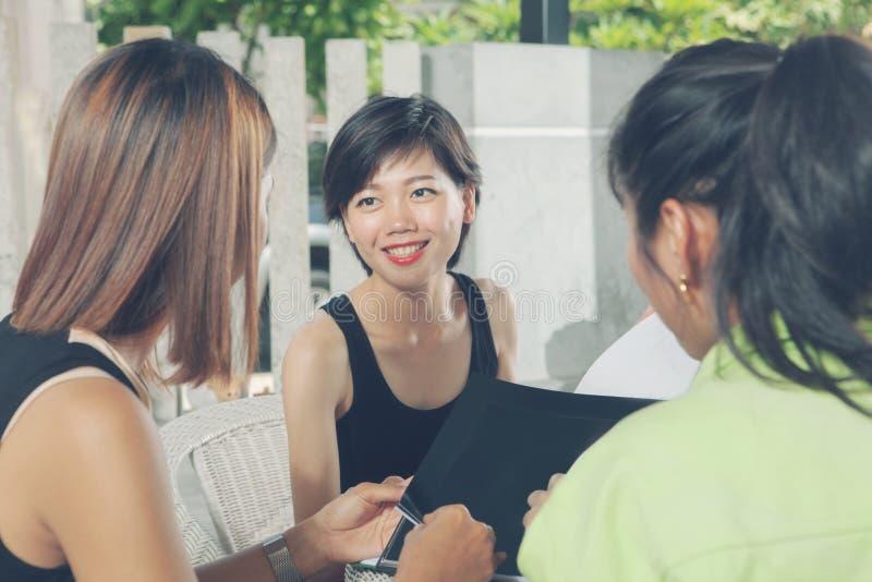 Un amigo asiático más joven de la mujer que habla con la relajación en casa de la vida fotos de archivo