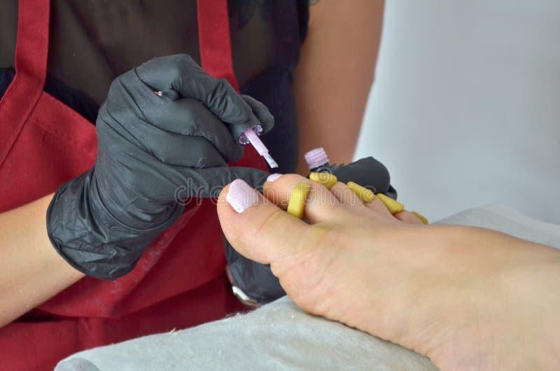 Un amo de la pedicura en un delantal rojo y guantes negros pinta los clavos de los pies de la muchacha con un esmalte de uñas ros foto de archivo libre de regalías