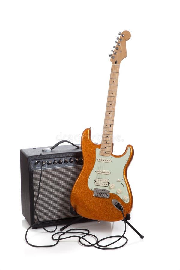 Un ampère e una chitarra elettrica su un fondo bianco immagine stock