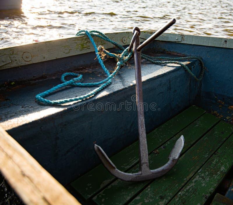 Un ancla grande del metal se sienta dentro de un pequeño barco que rema azul Tomado durante una puesta del sol temprana en un peq imágenes de archivo libres de regalías