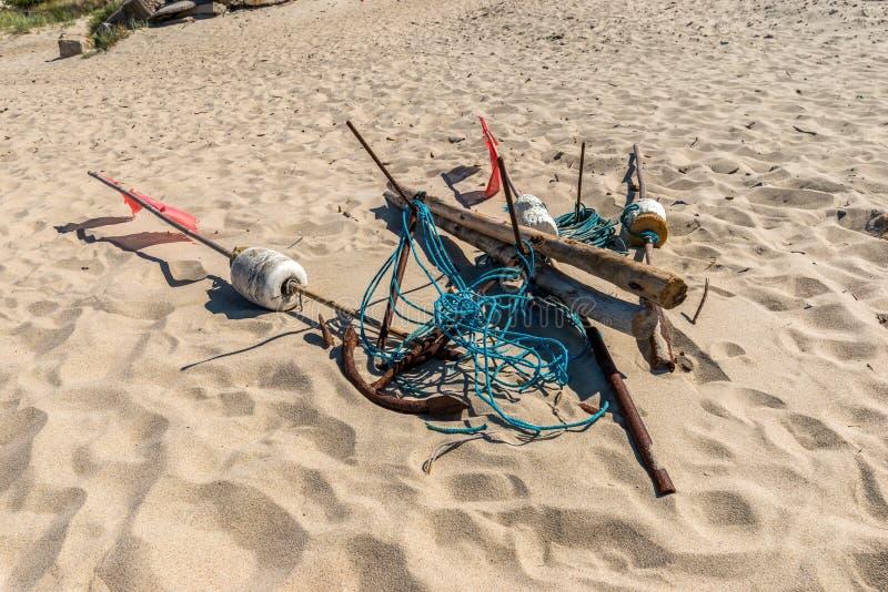 Un ancla vieja crujiente en una playa, línea azul, cuerda, nilón foto de archivo libre de regalías