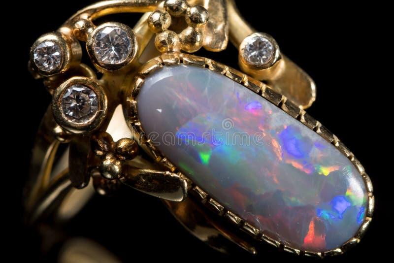 Un anello dorato con una pietra preziosa opalina variopinta fotografia stock libera da diritti
