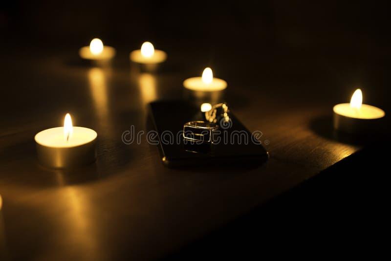 Un anello moderno del metallo con le candele brucianti nei precedenti fotografia stock libera da diritti