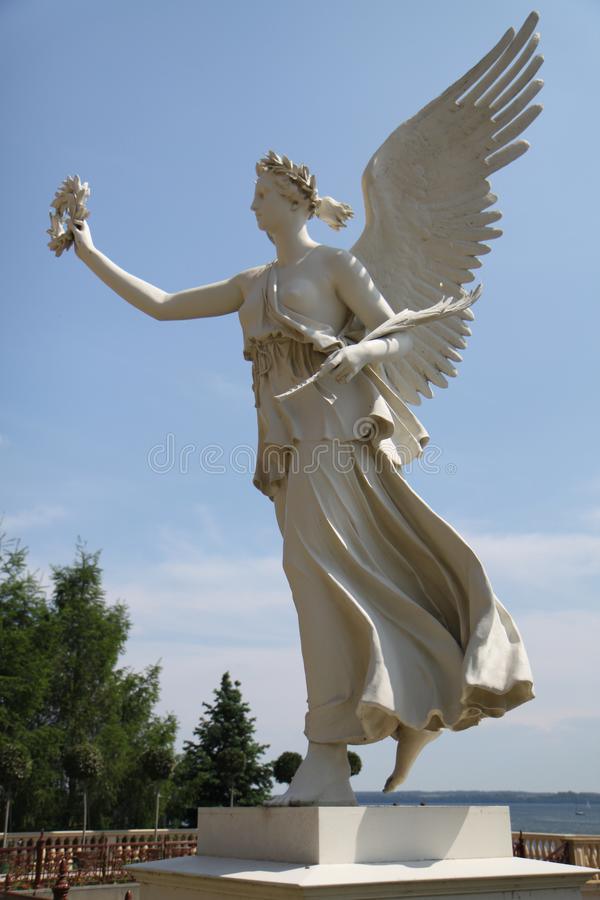 Un ange sur un piédestal près de l'eau photos libres de droits