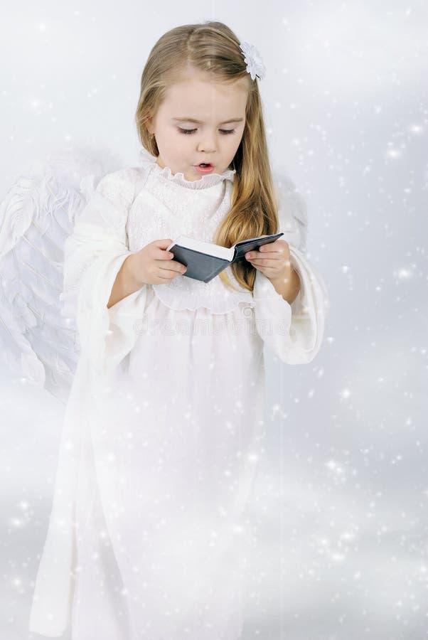Un angelo della bambina con un libro immagini stock