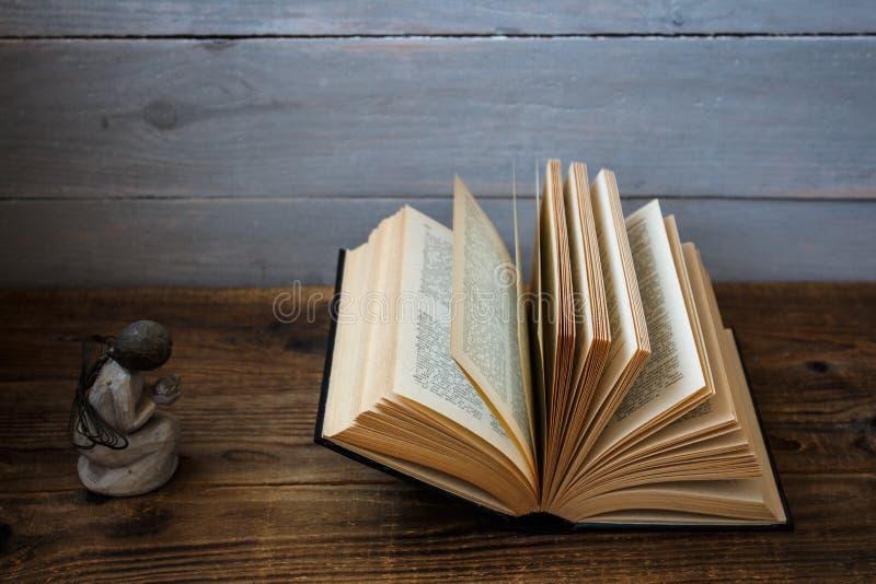 Un angelo e una bibbia aperta immagini stock libere da diritti