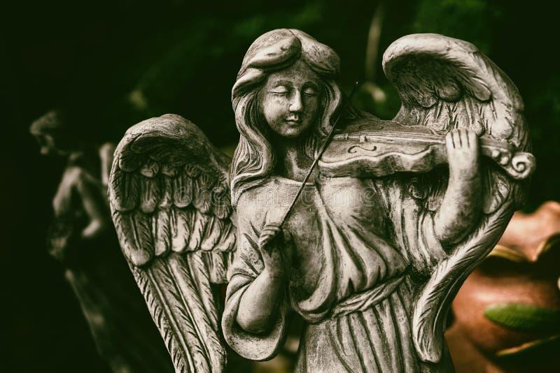 Un angelo femminile con capelli lunghi sta giocando il violino fotografia stock libera da diritti