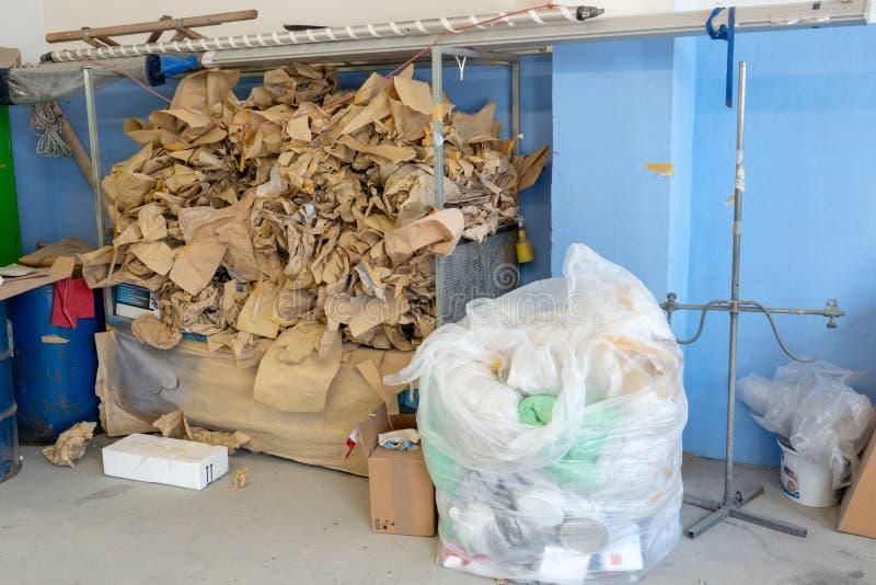 In un angolo di un'officina, una montagna di immondizia sta accatastando su fotografie stock libere da diritti