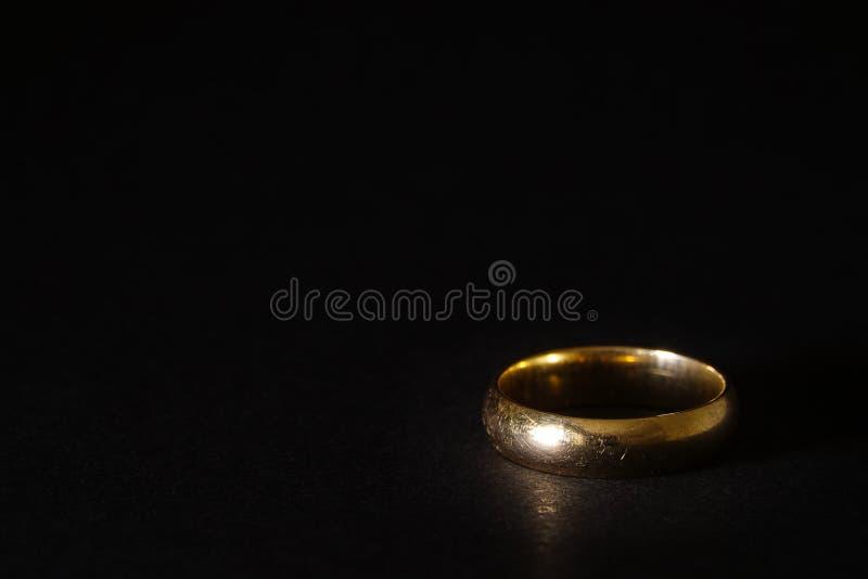 Un anillo de bodas usado rasguñado del oro viejo en fondo negro fotos de archivo