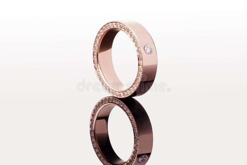 Un anillo de compromiso ancho del oro con el diamante en fondo uniforme con la reflexión Primer foto de archivo libre de regalías