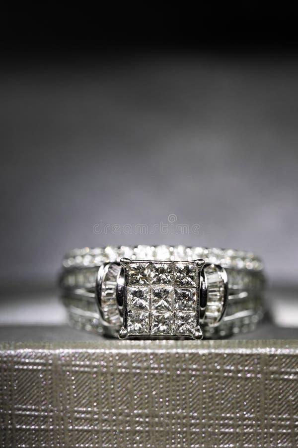 Un anillo de compromiso del diamante en una caja con destello/la reflexión Diamantes brillantes del princesa-corte imagen de archivo