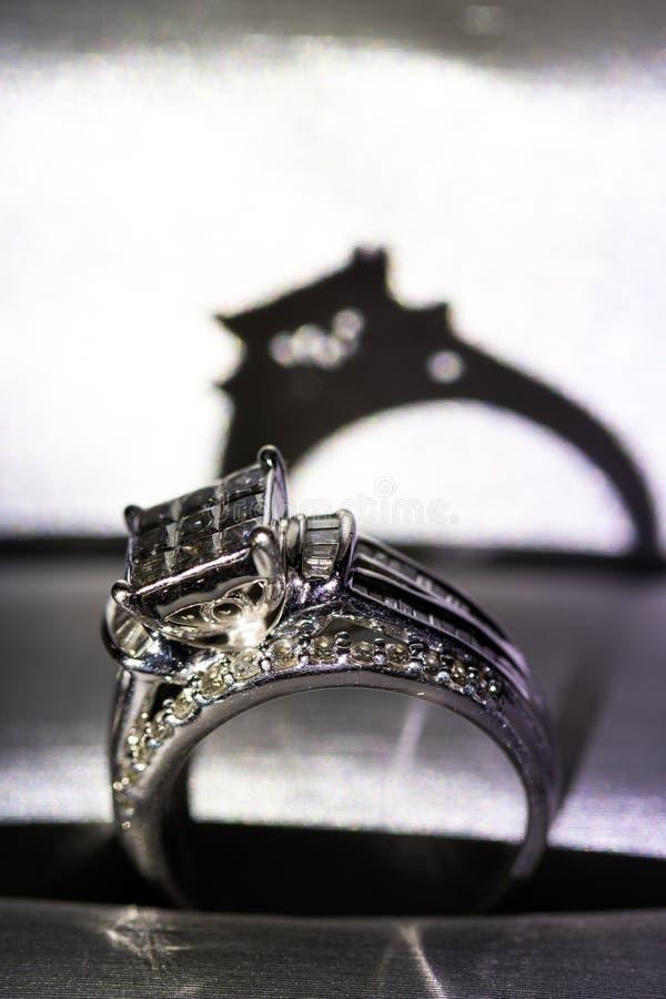 Un anillo de compromiso del diamante en una caja con destello/la reflexión Diamantes brillantes del princesa-corte foto de archivo