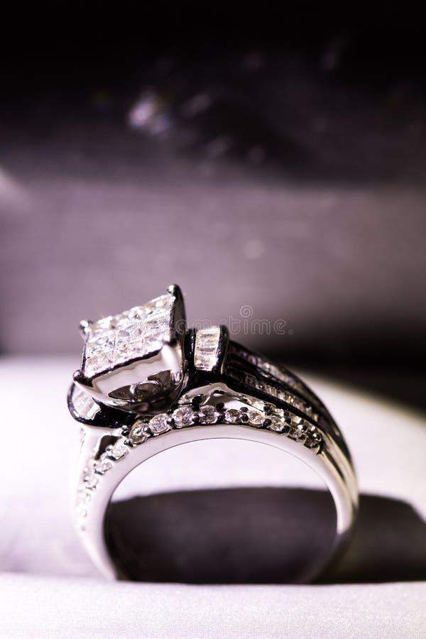 Un anillo de compromiso del diamante en una caja con destello/la reflexión Diamantes brillantes del princesa-corte fotos de archivo