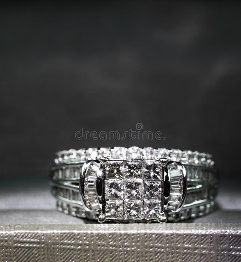 Un anillo de compromiso del diamante en una caja con destello/la reflexión Diamantes brillantes del princesa-corte imagenes de archivo