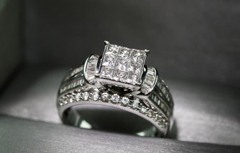 Un anillo de compromiso del diamante en una caja con destello/la reflexión Diamantes brillantes del princesa-corte foto de archivo libre de regalías