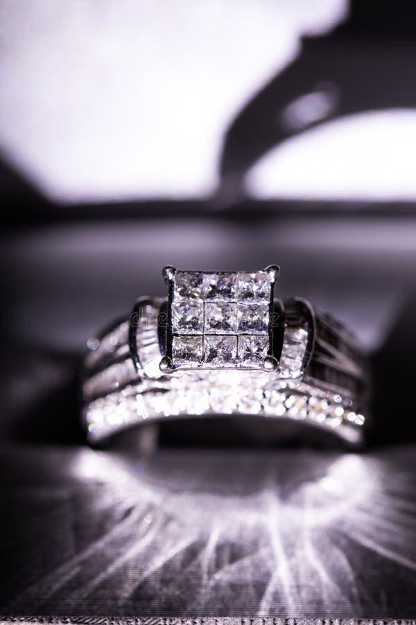 Un anillo de compromiso del diamante en una caja con destello/la reflexión Diamantes brillantes del princesa-corte imágenes de archivo libres de regalías