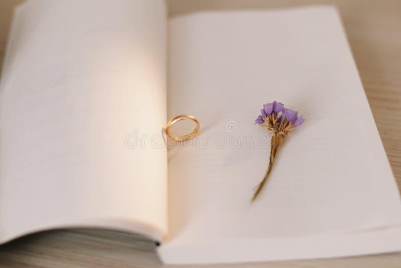 Un anillo de compromiso en el fondo de un libro y de una flor Oferta de la uni?n Detalles de la boda imagenes de archivo
