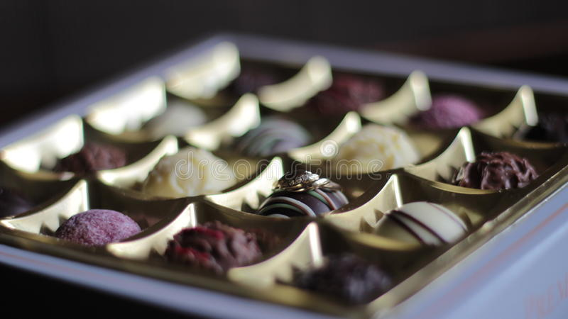 Un anillo de oro en una caja de lujo de chocolates imagen de archivo