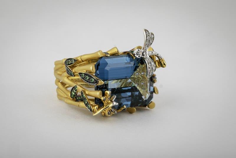 Un anillo de oro femenino con una piedra cuadrada azul en los bordes grises y verdes medios y pequeños, aislados en un fondo blan imagenes de archivo