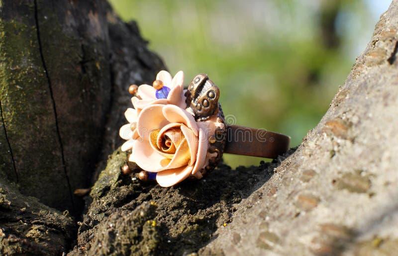 Un anillo hecho a mano en una forma de flores de la arcilla del pol?mero imagen de archivo libre de regalías