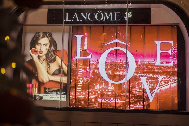 Un anuncio enorme para Lancome en la ventana de cristal de la tienda de la noche fotos de archivo