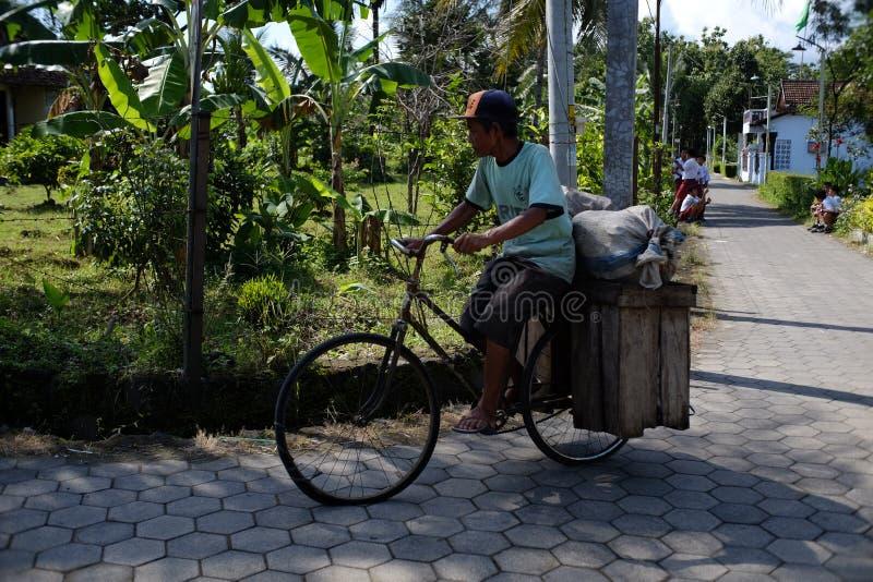 Un anziano usa la sua vecchia bicicletta modificata per trasportare merci fotografie stock