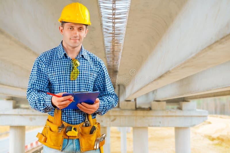 Un appaltatore sotto il ponte in costruzione fotografia stock