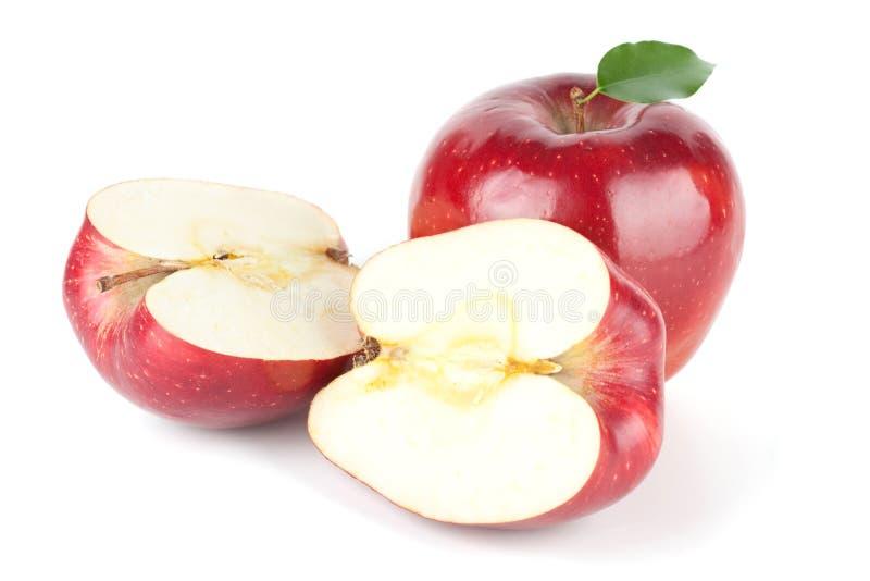 Un Apple rosso maturo con il foglio e due metà immagini stock libere da diritti