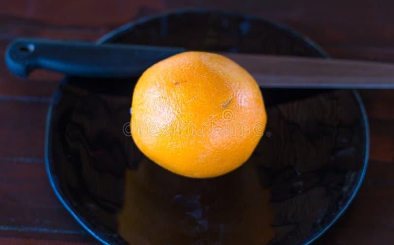 Un'arancia su un piatto servente attrative fotografie stock