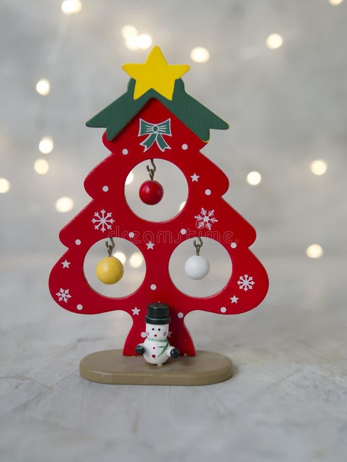 Un arbre rouge de Noël en bois avec l'étoile jaune, les petites boules colorées et le bonhomme de neige sur un fond gris des lumi image stock