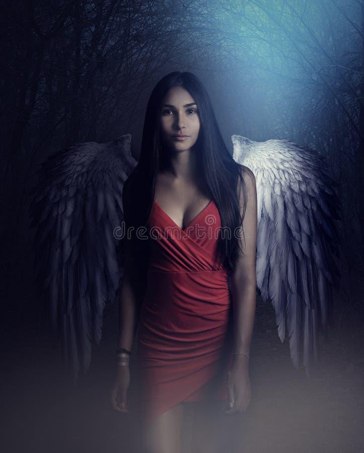 Un arcángel blanco hermoso descendido de cielo Una muchacha con un vestido rojo atractivo con las alas blancas enormes fotos de archivo libres de regalías