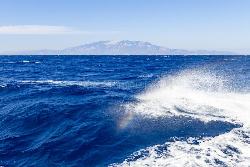 Un arc-en-ciel apparaît dans la vague d'arc du bateau pendant un voyage sur la mer autour de l'île de Zakynthos, Grèce images libres de droits