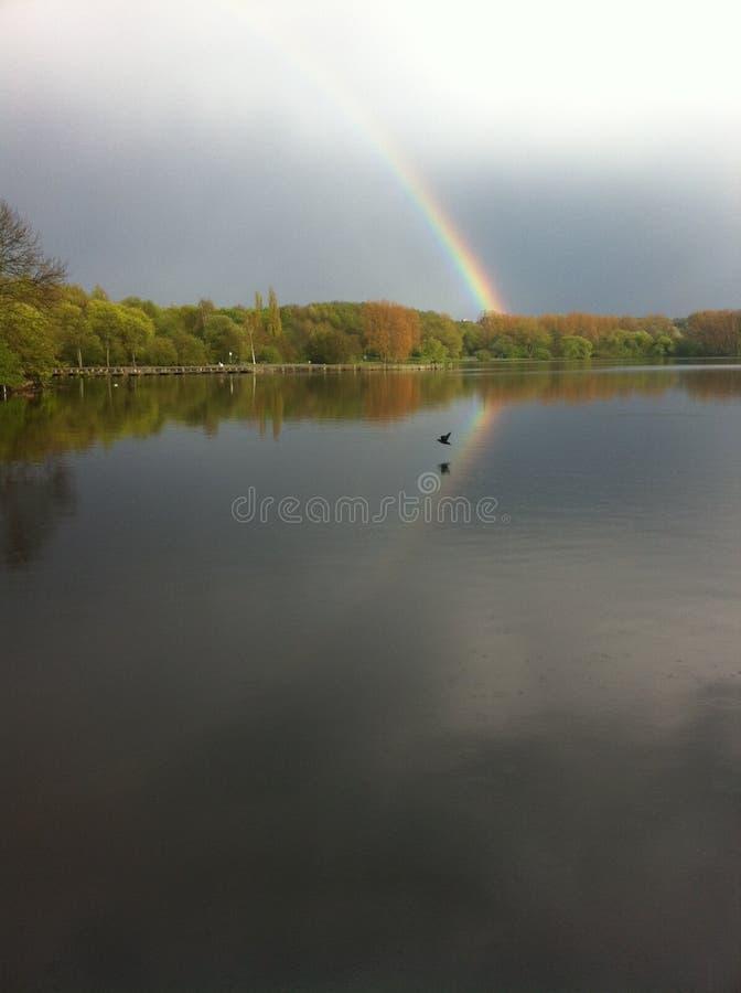 Un arc-en-ciel avec la r?flexion au-dessus du lac Umminger, Allemagne image libre de droits