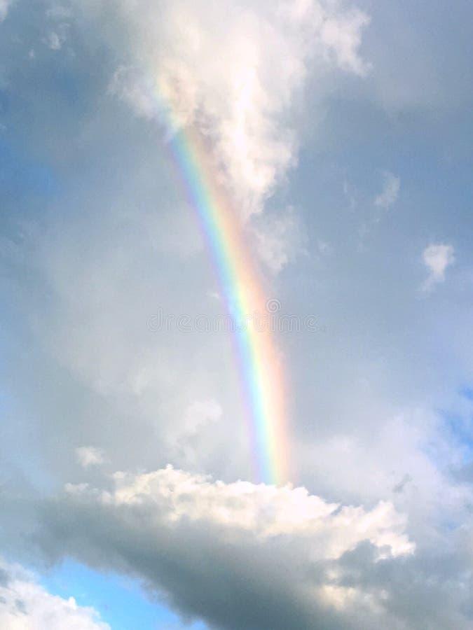 Un arc-en-ciel parmi les nuages photos stock