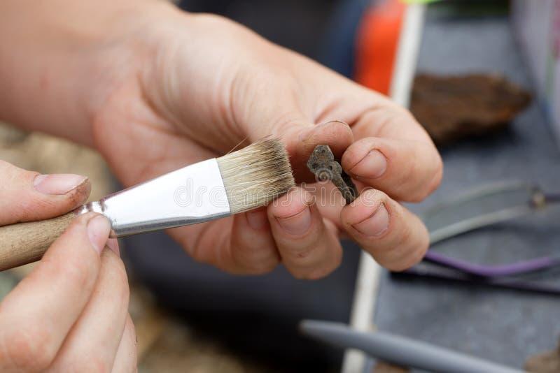 Un archéologue dégage les bijoux primitifs médiévaux images libres de droits