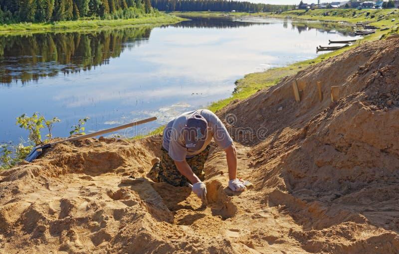 Un archeologo dell'uomo scava con attenzione fuori uno strato di suolo alla ricerca dei ritrovamenti immagine stock